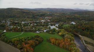 AX150_284 - 6K stock footage aerial video flying over Ammonoosuc River, approach small rural town, autumn, Woodsville, New Hampshire