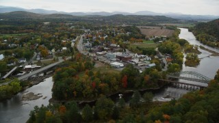 AX150_286 - 6K stock footage aerial video flying by rural town, bridge, Ammonoosuc River and Connecticut River, autumn, Woodsville, New Hampshire