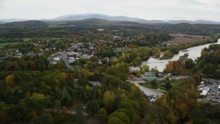 AX150_287 - 6K stock footage aerial video flying by small town near Connecticut River, autumn, Woodsville, New Hampshire