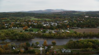 AX150_290 - 6K stock footage aerial video flying by small rural town, Connecticut River, autumn, overcast, Woodsville, New Hampshire