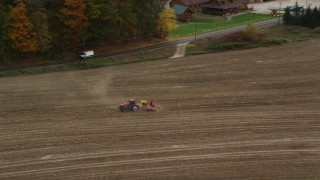 AX150_291 - 6K stock footage aerial video tracking a tractor on farmland, colorful trees in autumn, Woodsville, New Hampshire