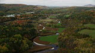 AX150_308 - 6K stock footage aerial video flying over small river, approaching a small river in autumn, Wells River, Vermont