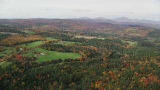 AX150_313 - 6K stock footage aerial video flying over bright forest, autumn, approach small farms, overcast,  Ryegate, Vermont