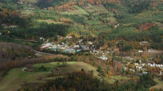 AX150_314 - 6K stock footage aerial video flying by small rural town, grassy clearings, foliage in autumn, Ryegate, Vermont
