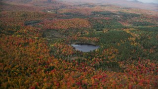 AX150_318 - 6K stock footage aerial video approaching pond, colorful forest and tilt down, autumn, Topsham, Vermont