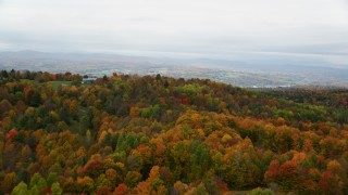AX150_339 - 6K stock footage aerial video flying over colorful forest, reveal rural homes, overcast, autumn, Barre, Vermont
