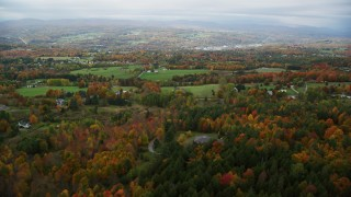 AX150_340 - 6K stock footage aerial video flying over rural homes, colorful foliage, autumn, overcast, Barre, Vermont