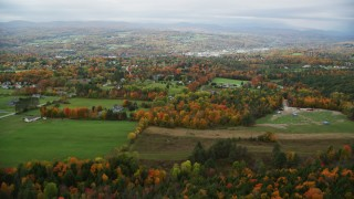 AX150_341 - 6K stock footage aerial video flying over rural homes, grassy clearings, trees in autumn, overcast, Barre, Vermont