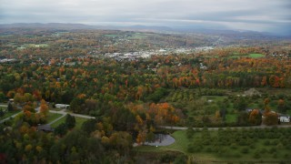 AX150_342 - 6K stock footage aerial video approaching and flying over rural homes, colorful trees in autumn, Barre, Vermont