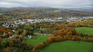 AX150_344 - 6K stock footage aerial video flying by homes, colorful foliage, downtown, autumn, Barre, Vermont