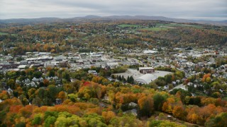 AX150_345 - 6K stock footage aerial video flying by homes, colorful autumn foliage, downtown, Barre, Vermont