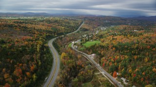 AX150_346 - 6K stock footage aerial video flying over Route 62,  Main Street near rural homes, colorful forest in autumn, Barre, Vermont