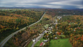 AX150_347 - 6K stock footage aerial video flying over Route 62, Main Street, approach rural homes, forest in autumn, Barre, Vermont
