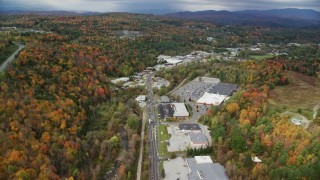 AX150_348 - 6K stock footage aerial video flying by strip malls, Main Street, colorful foliage in autumn, Barre, Vermont