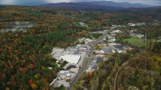 AX150_349 - 6K stock footage aerial video flying over colorful trees, strip malls on Main Street in autumn, Barre, Vermont