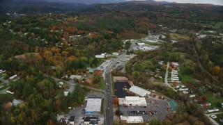 AX150_350 - 6K stock footage aerial video flying over strip malls, car dealership on Main Street, colorful trees, autumn, Barre, Vermont