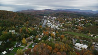AX150_352 - 6K stock footage aerial video flying over homes, approach small bridge, Winooski River, autumn, Montpelier, Vermont