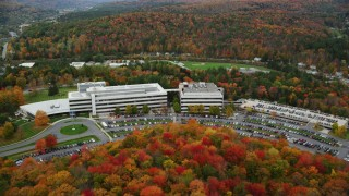 AX150_364 - 6K stock footage aerial video approaching office buildings, parking lots and tilt down autumn, Montpelier, Vermont