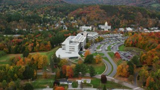 AX150_366 - 6K stock footage aerial video orbiting grassy clearings, colorful trees, office buildings, autumn, Montpelier, Vermont