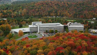 AX150_367 - 6K stock footage aerial video orbiting office buildings and colorful trees in autumn, Montpelier, Vermont