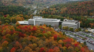 AX150_368 - 6K stock footage aerial video orbiting brightly colored trees, large office buildings, autumn, Montpelier, Vermont