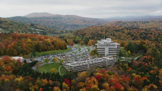 AX150_369 - 6K stock footage aerial video orbiting office buildings, dense, colorful trees in autumn, Montpelier, Vermont