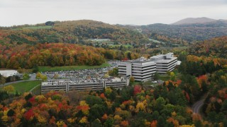AX150_370 - 6K stock footage aerial video orbiting office buildings, overcast skies, colorful trees, autumn, Montpelier, Vermont