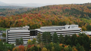 AX150_371 - 6K stock footage aerial video orbiting office buildings surrounded by brightly colored trees, autumn, Montpelier, Vermont