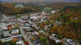 AX150_380 - 6K stock footage aerial video flying by downtown buildings, panning right to colorful trees, Montpelier, Vermont