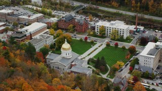 AX150_381 - 6K stock footage aerial video flying by Vermont State House, green lawns, colorful foliage, autumn, Montpelier, Vermont