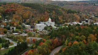 AX150_384 - 6K stock footage aerial video flying away from Vermont State House, by colorful trees, autumn, Montpelier, Vermont