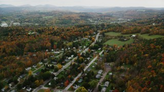 AX150_393 - 6K stock footage aerial video flying by neighborhood, grassy clearings, colorful foliage, autumn, Montpelier, Vermont