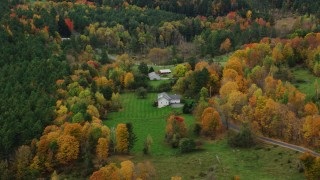 AX150_394 - 6K stock footage aerial video flying over rural homes, colorful trees, tilt down, autumn, Montpelier, Vermont