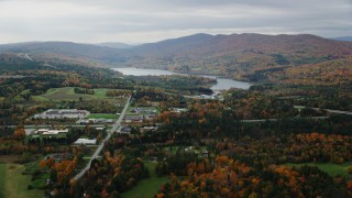 AX150_395 - 6K stock footage aerial video flying by Berlin Pond, colorful trees, autumn, overcast, Barre, Vermont