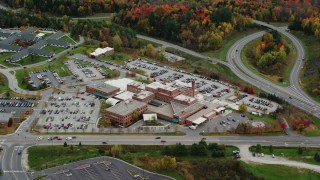 AX150_397 - 6K stock footage aerial video flying by Central Vermont Medical Center, roads, foliage in autumn, Barre, Vermont