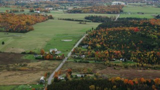 AX150_399 - 6K stock footage aerial video flying by rural farms, Airport Road, colorful trees, autumn, overcast, Barre, Vermont