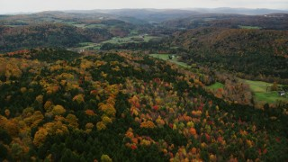 AX150_414 - 6K stock footage aerial video flying over colorful forest, approaching farms, autumn, overcast, Bethel, Vermont