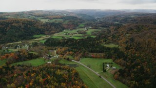 AX150_415 - 6K stock footage aerial video flying over Route 14, Randolph Center Road and farms in autumn, Bethel, Vermont