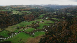 AX150_416 - Aerial stock footage of Flying by Route 14 through farms in autumn, overcast day, Bethel, Vermont