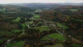 AX150_417 - 6K stock footage aerial video flying over Route 14, farms, rural homes and small town, autumn, Bethel, Vermont