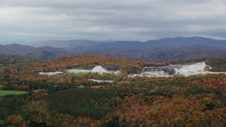 AX150_419 - 6K stock footage aerial video flying by a colorful forest, quarry, autumn, overcast, Bethel, Vermont