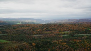 AX150_421 - 6K stock footage aerial video flying by colorful forests and hills in autumn, overcast sky, Bethel, Vermont