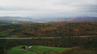 AX150_422 - 6K stock footage aerial video flying by forest of colorful trees, hills in autumn, overcast day, Bethel, Vermont