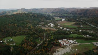 AX150_423 - 6K stock footage aerial video flying over trailers, approaching White River, Route 107 in autumn, South Royalton, Vermont