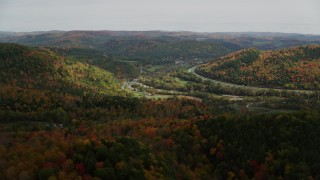 AX150_425 - 6K stock footage aerial video flying over colorful forest, hills, approach small farms, autumn, South Royalton, Vermont