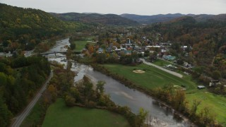 AX150_428 - 6K stock footage aerial video flying by small bridge, White River, small rural town, autumn, South Royalton, Vermont