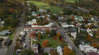 AX150_432 - 6K stock footage aerial video orbiting shops and town square in a small town, autumn, South Royalton, Vermont