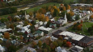 AX150_433 - 6K stock footage aerial video orbiting homes, churches in a small town, autumn, South Royalton, Vermont