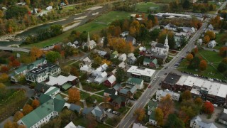 AX150_439 - 6K stock footage aerial video orbiting town square, churches, small rural town in autumn, South Royalton, Vermont