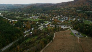 AX150_440 - 6K stock footage aerial video approaching White River, small bridge, small rural town in autumn, South Royalton, Vermont